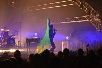 Metric frontwoman Emily Haines brings out a neon green butterfly cape in the Mooselight Blues tent.