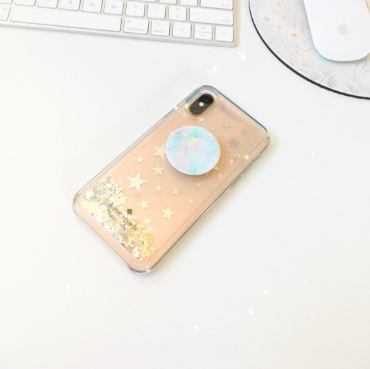 A photo of my gold iPhone XS, in my glittery Kate Spade case with an ever trusty PopSocket stuck to it.