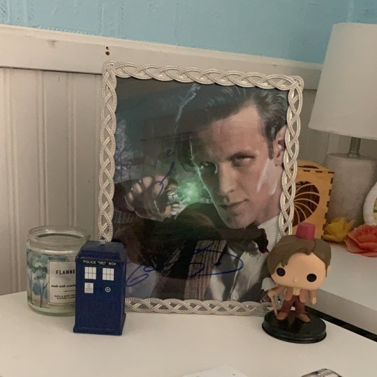 My signed photo, next to an Eleven Funko Pop and a TARDIS figurine.