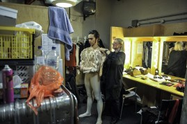 Johanna Doring secures Jason Reilly's costume in the dressing room