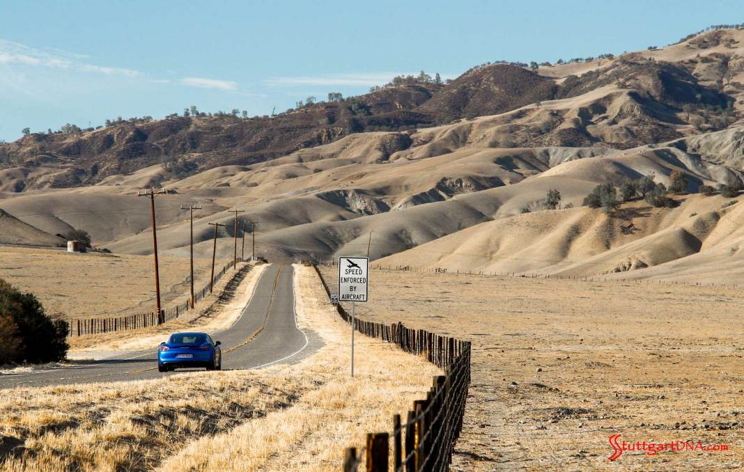 Porsche SE acquires INRIX stake: An aesthetic shot of a Blue Cayman GTS, rear view, on a desolate oak-and-savanna road near Laguna Seca. Credit: Porsche AG