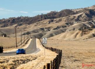 Porsche SE acquires INRIX stake: An aesthetic shot of a Blue Cayman GTS, rear view, on a desolate oak-and-savanna road near Laguna Seca. Credit: Porsche AG