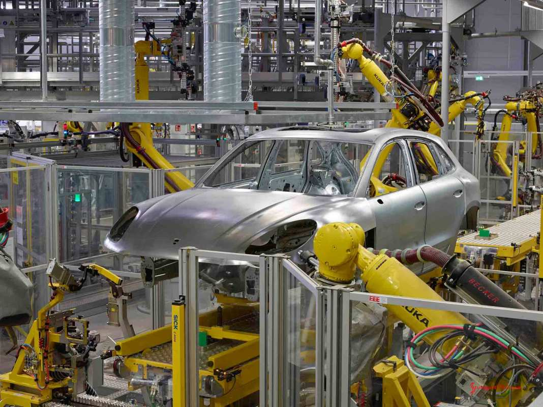 Porsche June 2017 USA sales - A Macan shell is seen here at the Leipzig among and being assembled by yellow-colored robots. Credit: Porsche AG