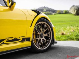 March 2018 Porsche USA sales: Pictured here is a racing-yellow Porsche 911 GT3 RS at rest, its right front corner viewed from the side. Credit: Porsche AG