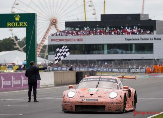 Porsche wins both 2018 Le Mans 24-Hour GT classes: Seen here in vivid relief is the No 92 Pink Pig RSR tking th checkered flag, with PEC in bg. Credit: Porsche AG