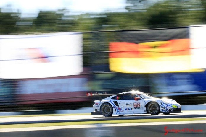 Porsche wins 2018 Petit Le Mans: Seen here from its right side is the No. 912 speeding down the track, with a blurry German flag in f.g. Credit: Porsche AG