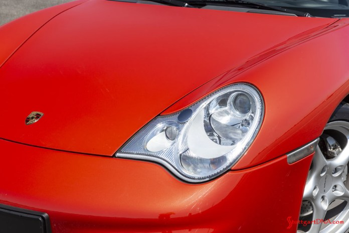 "996-gen Porsche 911 Buyer Guide: Viewed here in a medium shot is a 996 Carrera 4's revised left headlight against the car's orange-colored 996 body. This revision was an act of appeasement for the 996's über-purists' disdain for their so-called ""fried-egg"" original headlights. Credit: Porsche AG"