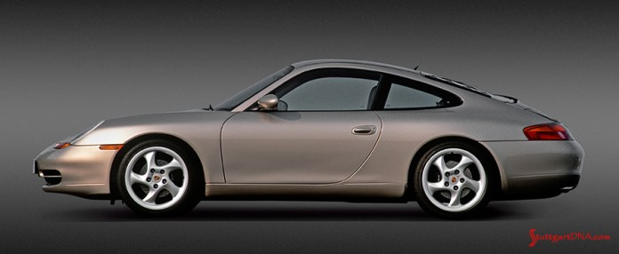 996-gen Porsche 911 Buyer Guide: This is a PR / brochure photo of a 996 Carrera tan coupe, viewed from its left side, in an interior studio setting. Credit: Porsche AG