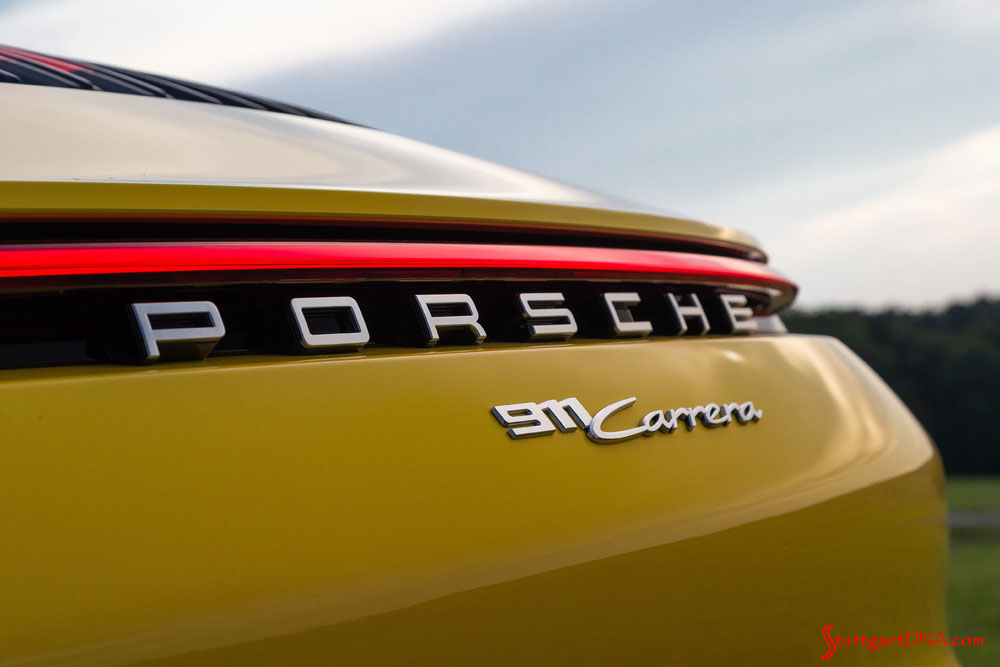 "October 2019 USA Sales: This photo is a tight shot of the rear ""Porsche 911 Carrera"" badging and illuminated continuous red taillight strip on a Racing Yellow 911. Credit: Porsche AG"