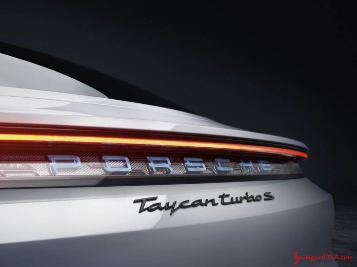 Porsche Taycan first electric sports car world premiere: Seen here is a white Taycan Turbo S's rear badging, as photographed inside a studio. The continuous light bar is illuminated above it. Credit: Porsche AG
