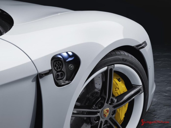 Porsche Taycan first electric sports car world premiere: This is a tight shot of a white Taycan's charging connections and right-front PCCB brake's humongous yellow caliper. Credit: Porsche AG