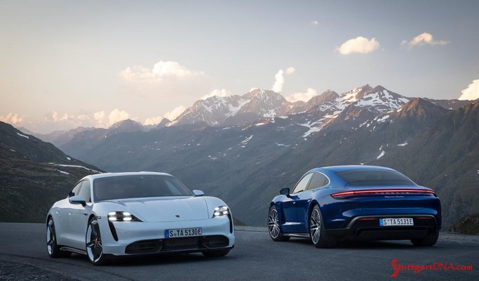 Porsche Taycan first electric sports car world premiere: Pictured here are two white and blue Taycans poised on a hilltop in the mountains. Credit: Porsche AG