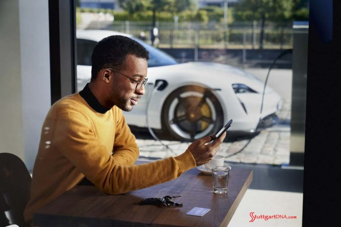 Porsche launches Porsche Finder, its pre-owned vehicle search platform - Pictured here is an African American man operating his smartphone, with his Taycan charging in b.g. Credit: PCNA