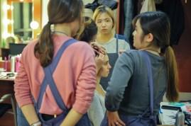 Joana Romaneiro wird von unseren Kollegen aus der Maske für die Vorstellung vorbereitet, die Koreanischen Mitarbeiter schauen aufmerksam zu.