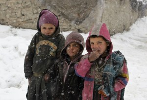 Internally displaced Afghan children pose for a photo as they stand in the snow outside their shelter at a refugee camp in Kabul