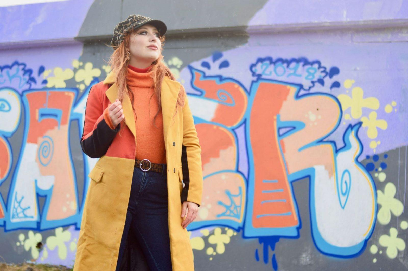 Blogger Twenty-Something City wears orange jumper and camel coat
