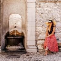 Italian Inspired: Black Bodysuit, Red Vintage Polka Dot A-line Skirt, Classic Oversized Straw Hat, Gold Sphere Earrings, Round Rattan Bag, Black Cat-Eye Sunglasses, and Leaf Detail Rose Gold Sandals