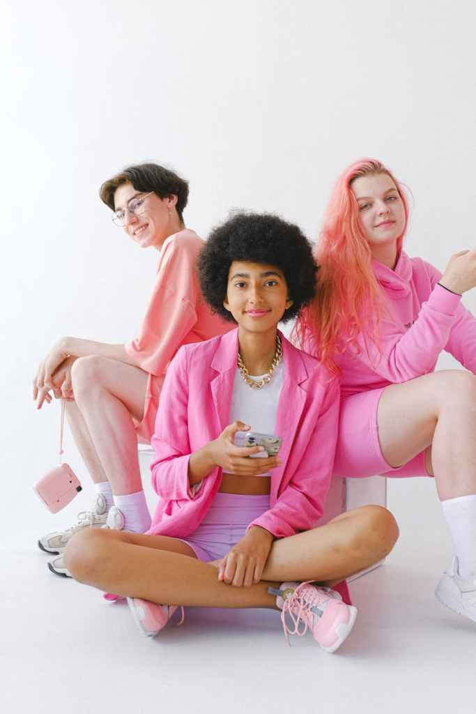 happy multiracial teenagers in trendy clothes with gadgets