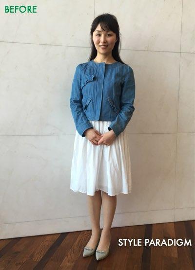 ブルーのノーカラージャケットと白の膝丈スカートを着た女性