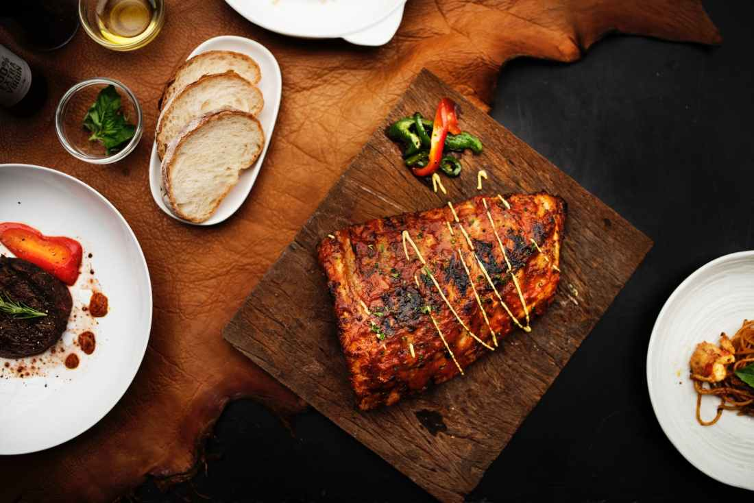 flat lay photography of grilled meat on brown chopping board