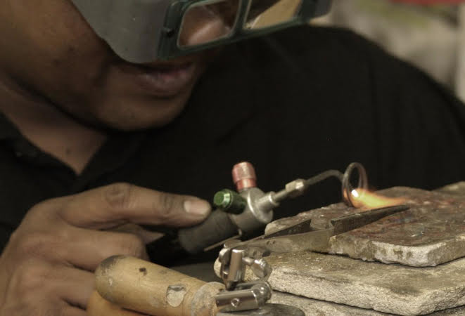 Craftsman soldering the jewelry. www.google.com