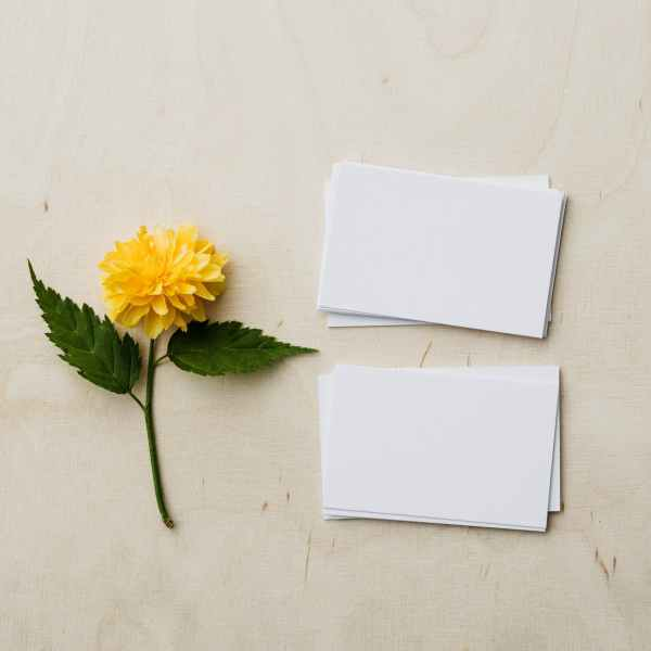 blank mockup business cards and yellow flower on desk