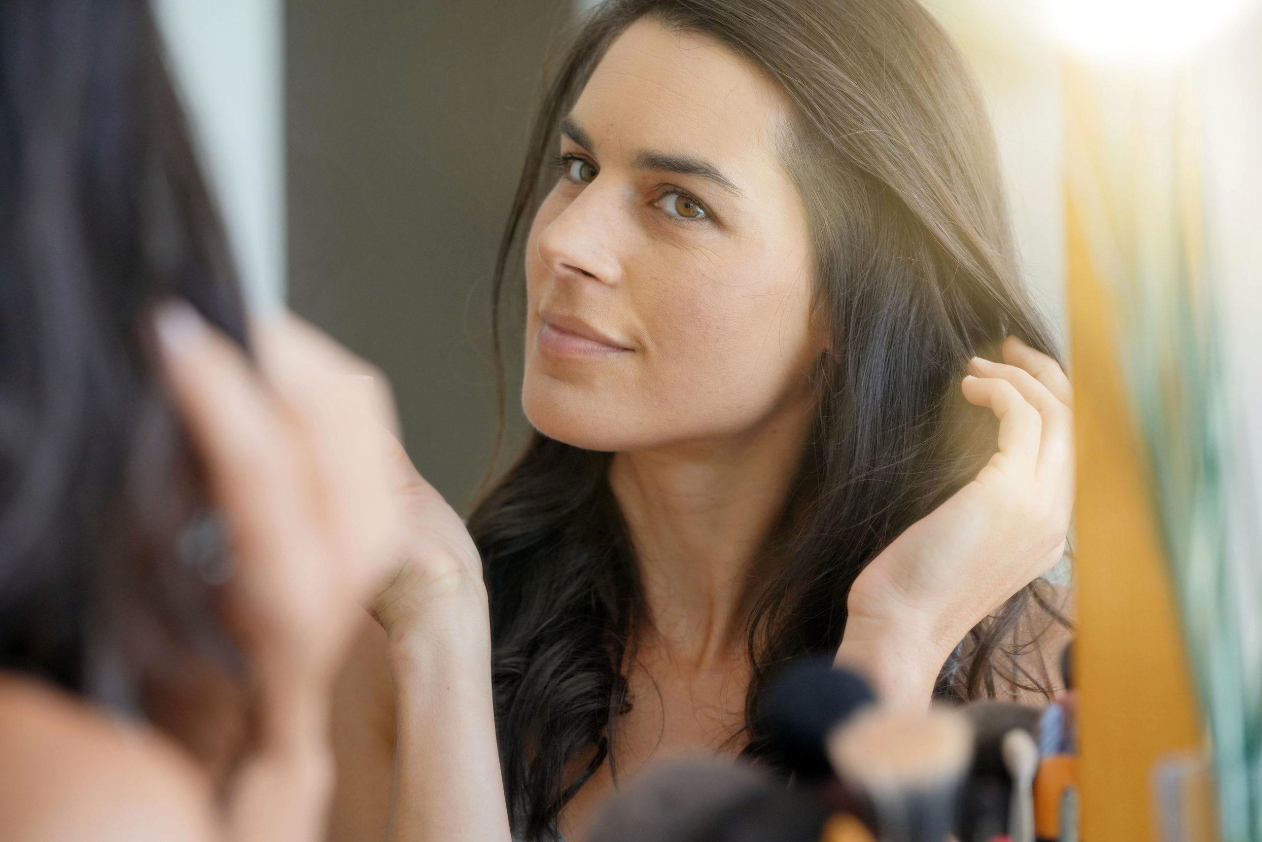Frau betrachtet sich im Spiegel - Kollagen