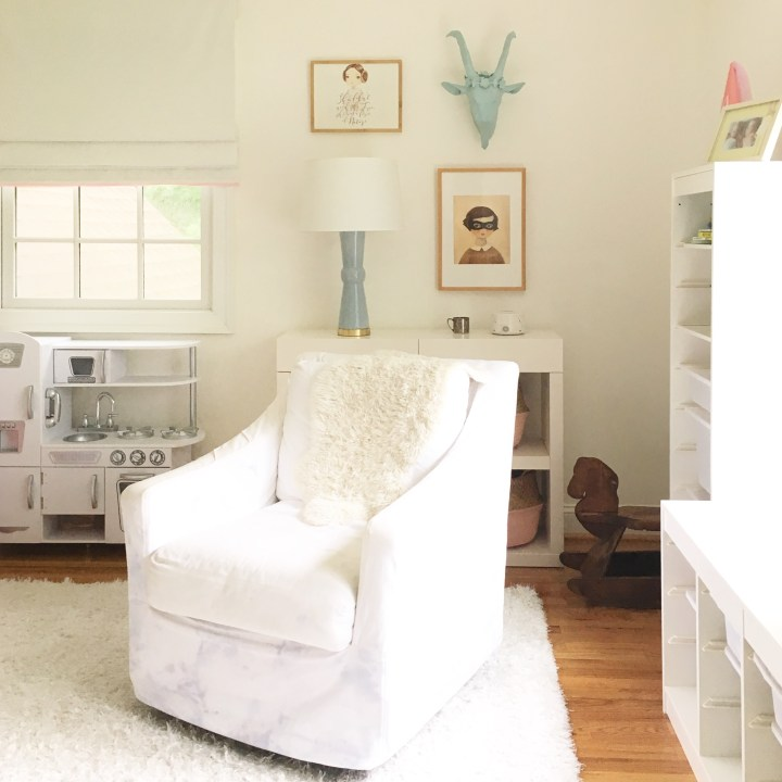 Girls bedroom featuring sweet art prints, a blue table lamp, white nursery glider and roman shades with pink pom pom trim