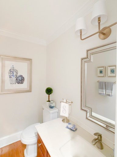 Styling Gypsy Interior Design traditional powder room featuring a warm wood vanity, geometric beaded mirror, aged brass triple sconce, blue and white ginger jar, preserved boxwood topiary, framed agate slice art and other bathroom decor.