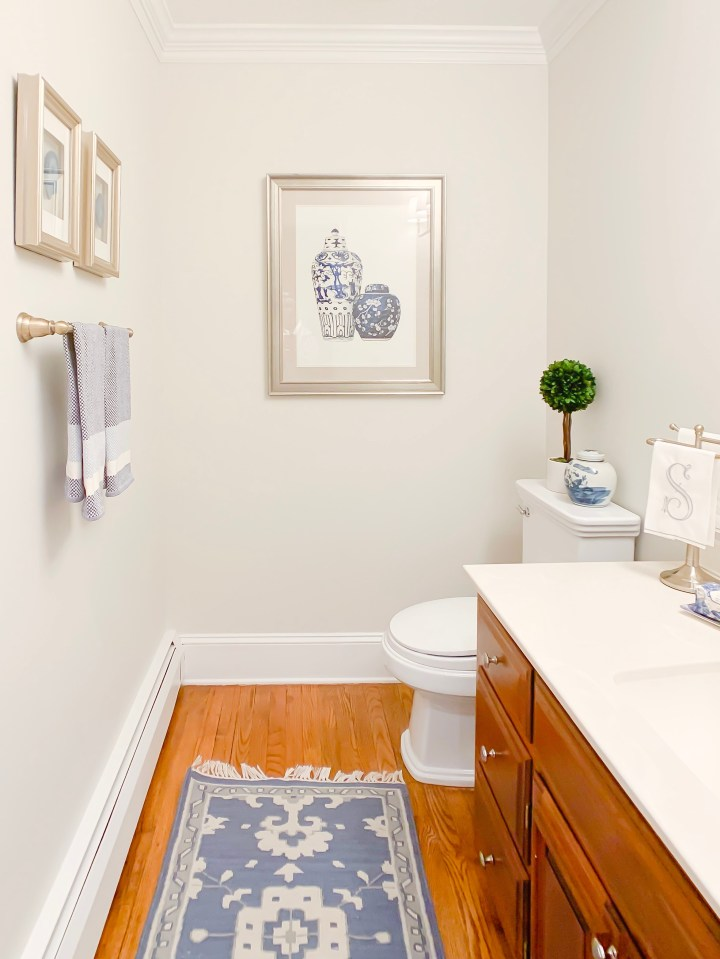 Styling Gypsy Interior Design traditional powder room featuring a warm wood vanity, blue traditional Caitlin Wilson rug, aged brass bathroom hardware, blue and white ginger jar, classic framed art, preserved boxwood topiary and other bathroom decor.