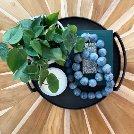 Styling Gypsy Interior Design clean and current family room design featuring round teak starburst coffee table and coffee table styling with fresh greenery, soft blue bead decor, and black metal tray