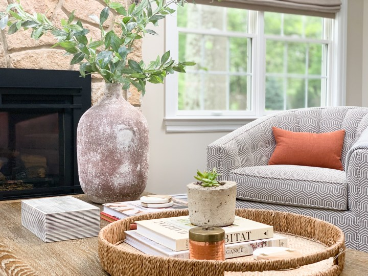 Styling Gypsy Interior Design bright and airy living room design featuring cream paint, gray swivel chairs, rust pillows, natural stone fireplace, warm wood coffee table, rustic terracotta urn with branches, rattan tray, copper decor and thoughtful accessories.