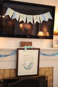Watercolored painting hung on mantle with initials