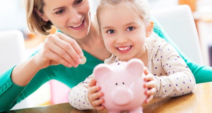 Mãe e filha colocando dinheiro no cofrinho, ilustrando uma das atividades da educação financeira infantil.