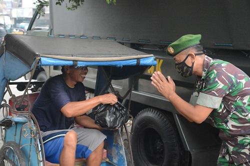 MEMBAGIKAN SEMBAKO : Anggota Korem 071/Wijayakusuma membagikan paket sembako kepada tukang becak, Selasa (7/4). (SM/dok)