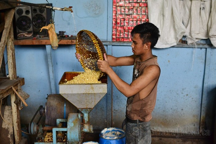 Arif, salah seorang pekerja asal Sukabumi sedang memasukan kacang kedelai untuk dihaluskan. (Foto: Fajrul Islam/SJ)