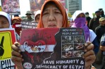 "Seorang ibu memegang poster ""SAVE HUMANITY & DEMOCRACY OF EGYPT"". (Foto: Fajrul Islam/SuaraJakarta)"