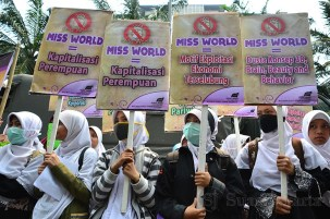 Para pengunjuk rasa memegang poster tolak miss world di depan gedung MNC Tower, Jakarta (5/9). (Foto: Fajrul Islam/SJ)