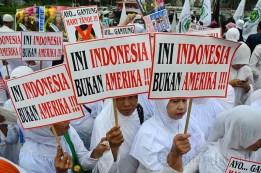 """Beberapa ibu-ibu membawa poster """"Ini Indonesia, Bukan Amerika' sebagai bentuk penolakan terhadap Miss World 2013. (Foto: Fajrul Islam/SJ)"""