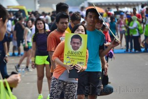Penonton menunggu sambil membawa poster peserta Jakarta Marathon Festival 2013. (Foto: Fajrul Islam)