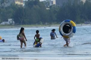suara-jakarta-Para-Pengunjung-sedang-asik-mandi-pantai-di-tengah-tengah-aksi-bersih-pantai