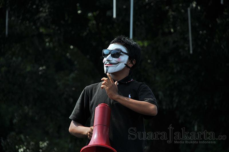 Salah seorang orator aksi mengenakan topeng vendetta sebagai simbol perlawanan. (Foto: Fajrul Islam/SuaraJakarta)