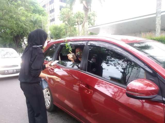 membagikan bibit pohon kepada pengguna jalan yang melintas di persimpangan Jalan Lambung Mangkurat