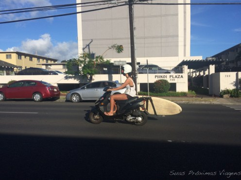Surfista transportando a prancha de scooter em Oahu