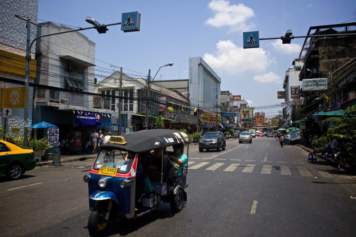 A tuk-tuk barrels down a street in Bangkok, Thailand.