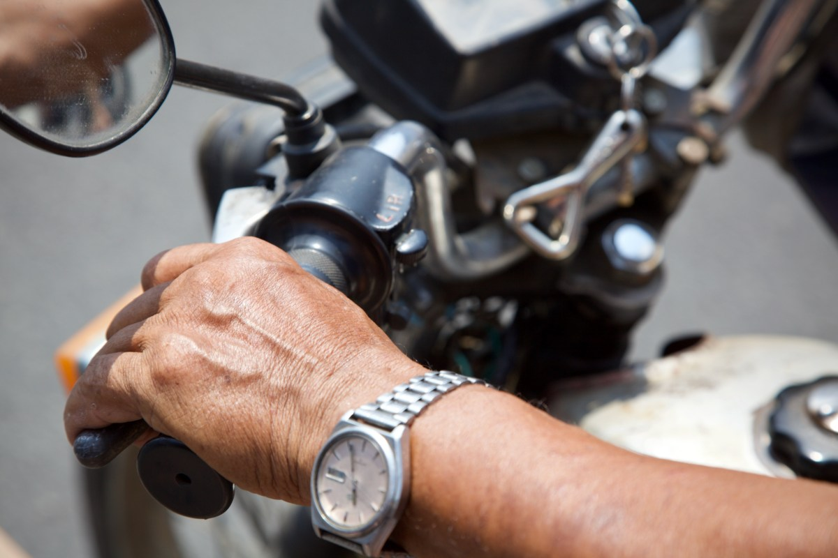 A photograph of a man's hand holding the handlebars of a motorcycle.