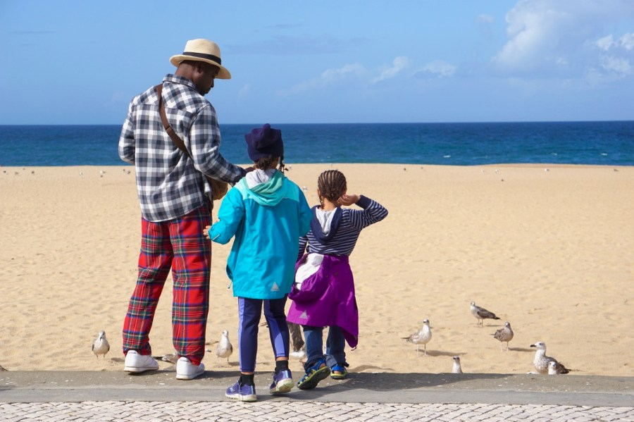Bertrand and the girls feeding the birds at the beach in Nazare, Portugal
