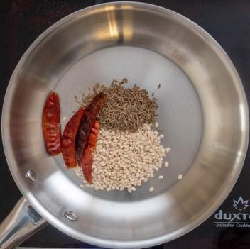 Roast spices and urad dal for Keerai Molagootal recipe