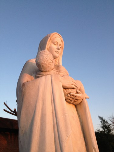 Setting sun casts a warm light on the Madonna outside Our Lady of the Holy Souls church in Little Rock.