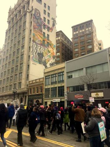 Oakland Women's March protestors with huge mural in background. Downtown Oakland